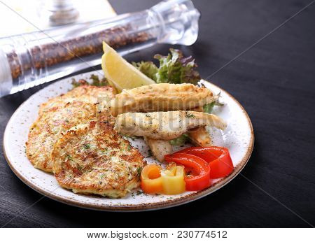 Fried Fish With Zuccini Pancakes On A Plate. Omega3 With Vegetables
