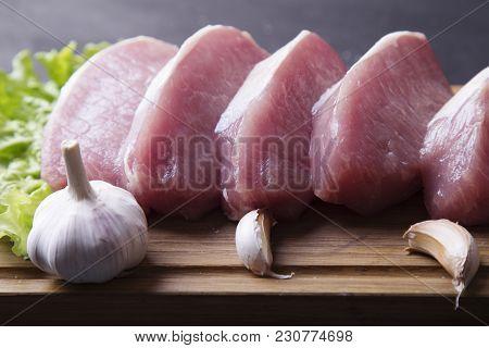 Fresh Raw Pork Fillet Slices On Wooden Board With Fresh Garlic