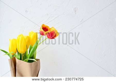 Bouquet Of Yellow And Orange Tulips In A Kraft Paper On A White Background, Concept Of Women's Day O