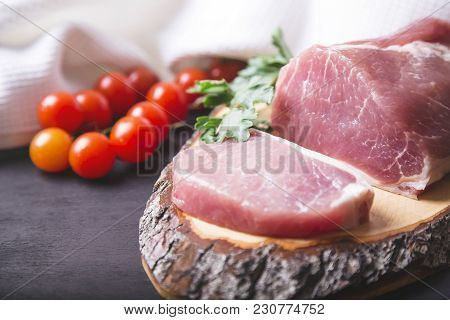 Raw Pork Sliced Meat With Tomatoes On Wooden Board