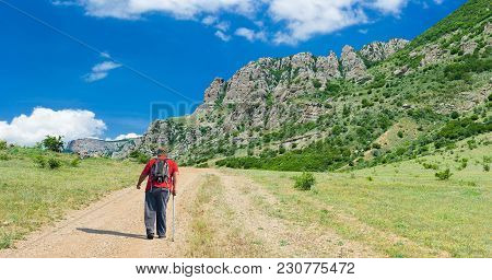 Lonely Hiker On The Remote Road To Valley Of Ghosts In Crimean Mountains