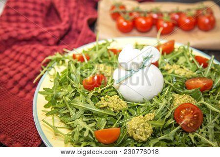 Italian Burrata Cheese With Arugula, Pesto Sauce And Cherry Tomatoes . Tasty Food