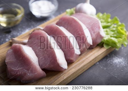 Raw Slice Pork On Wooden Board With Spices And Olive Oil