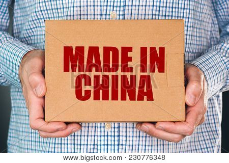 Man holding cardboard box product package with Made in China label imprint for merchandise goods imported from East Asia poster