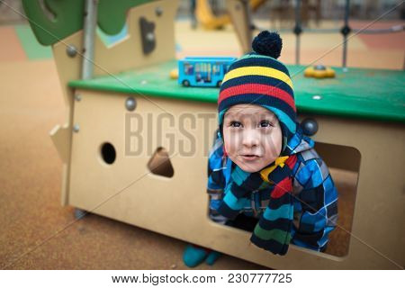 Beautiful Child Sits In Small House At The Playground Area. Pensive Little Boy Dreams And Mysterious