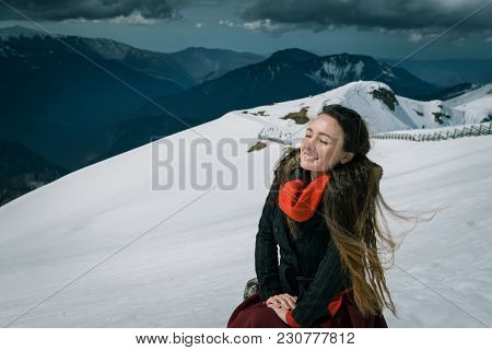 Young Woman Sits On The Top Of Snowy Mountains In The Ski Resort. Trendy Traveler Enjoys Wonderful D