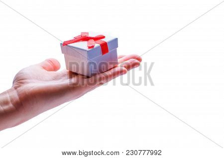 Hand Holds Gift Box In Hand Isolated In White Background. Gift With Red Bow. Christmas Or Xmas Scene