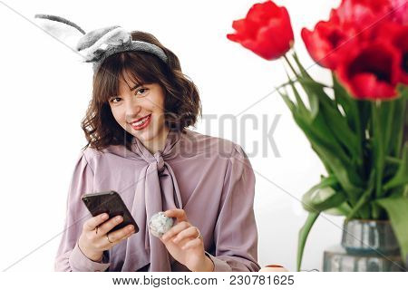 Beautiful Stylish Girl In Bunny Ears Smiling And Painting Easter Eggs On Rustic Table And Holding Ph