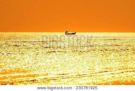 Silhouette Of Fishermen On A Fishing Boat In The Sea. And Evening Golden Light.