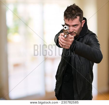 young man pointing with gun at a house