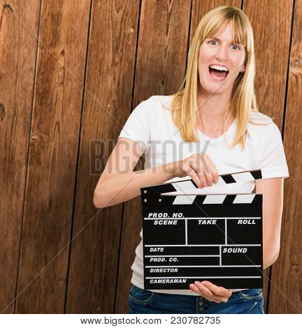 pretty woman holding a clapper board against a wooden background