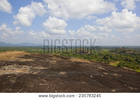 Volcanic Rock Overlooking A Sri Lankan Scenic Vista With Woodland And Mountains Under A Blue Sky Wit