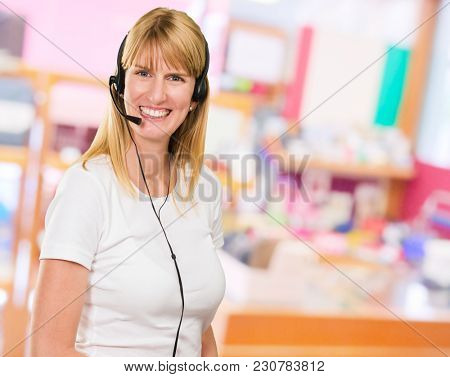 Happy Woman On Headset at a hotel reception, indoor