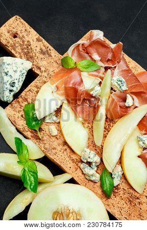 Italian Food With Melon, Prosciutto And Cheese On Cork Cutting Board. Dark Concrete Background