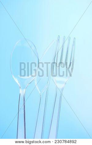 Plastic silverware on blue background