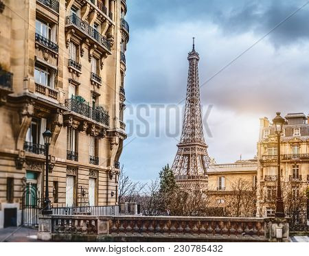 small paris street with view on the famous paris eifel tower on a cloudy rainy day with some sunshine - wide horizontal panorama poster