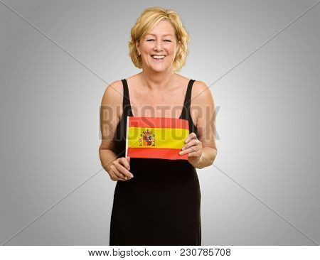Happy Mature Woman Holding Spain Flag Isolated On Grey Background