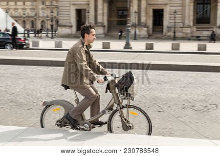 Paris, France - March 28, 2017: Man rides in Paris on self-service bike rental
