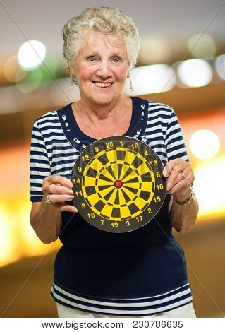 Happy Mature Woman Holding Dart Board, Indoors