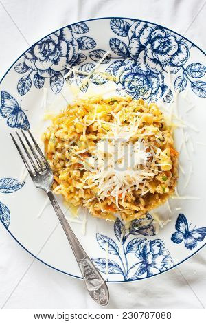 Portion Of Risotto With Pumpkin On Plate With Blue Ornament On White Table