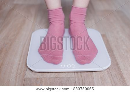 Legs Of A Young Woman Measuring Her Weight On A Modern Smart Scales.