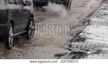 The Car Drives Past The Pothole With Puddles On The Road.