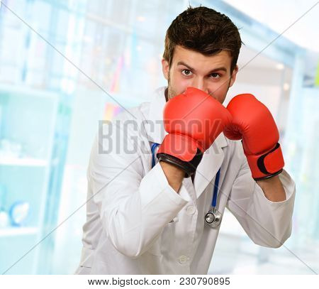Young Doctor Wearing Boxing Gloves Covering Mouth, Indoor