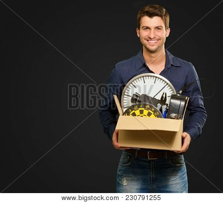 Portrait Of Happy Man Holding Cardboard Box On Black Background