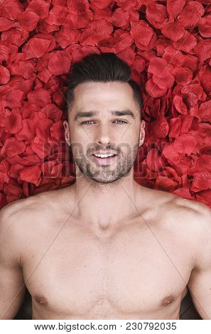 Handsome young man lying in rose petals