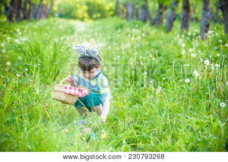 Cheerful Boy Holding Basket Full Of Colorful Easter Eggs Standing On The Grass In The Park After Egg