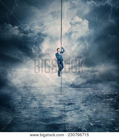Businessman Salvation, Surviving The Storm Buiness Concept As A Scared Man Hanging On A Chain Above
