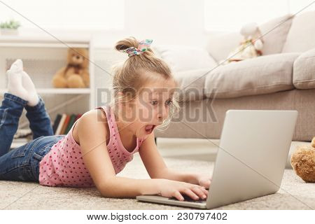 Scared Little Casual Girl Watching Movie. Frightened Female Kid Lying On The Floor, Home Alone, Watc