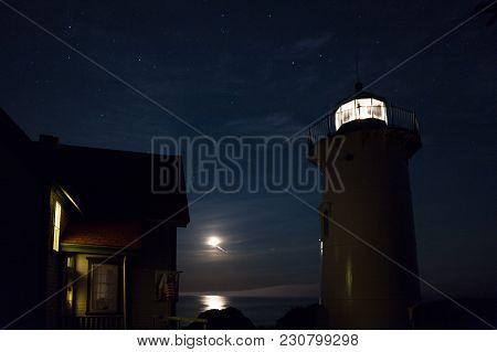 Little River Lighthouse Near Cutler, Maine, Shines Brightly In The Foreground, As The Moon Reflects