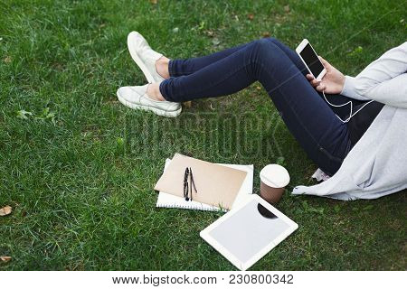 Young Unrecognizable Woman Sitting Outdoors On Grass With Digital Tablet, Typing, Surfing Internet,