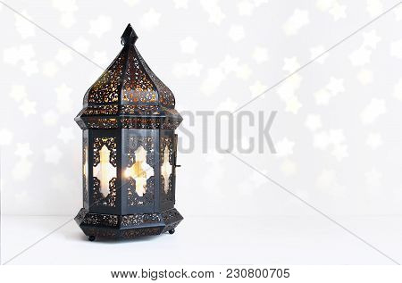 Ornamental Dark Moroccan, Arabic Lantern On The White Table. Burning Candle, Glittering Bokeh Lights