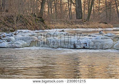 A Small, Narrow River With A Waterfall - A Small Water Threshold. The Edges Are Covered With Dry, Br