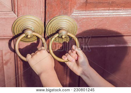 The Hand Opens The Antique Door By The Round Handle.