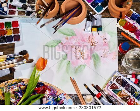 Authentic paint brushes still life in art class school. Group of brush in clay jar. Orange tulip in the foreground. Copy space for text. Spring discounts on drawing course.