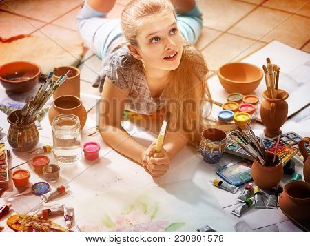 Authentic artist children girl paints with set palette watercolor paints palette and brush in morning sunlight . Painting in studio on floor. Child dreams of going to art school.