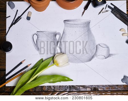 Drawing picture on table in art class school. Group of brush in clay jar on wooden table. Flowers as symbol of spring discounts. Training art graphics courses by nib pen. Sale of artistic goods.