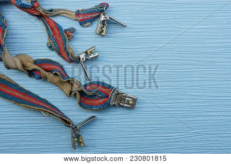 Old Colored Suspenders On A Blue Table