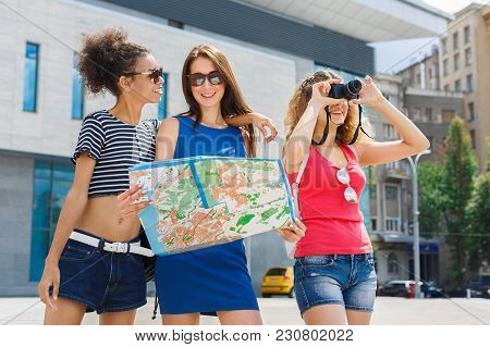 Three Happy Girls With Paper Map Outdoors. Female Friends Walking Around Summer City, Taking Photos