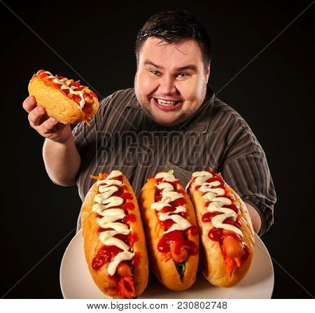 Fat man eating fast food hot dog on plate. Breakfast for overweight person. Junk meal leads to obesity. Person regularly overeats concept on black background. Health problems due to malnutrition.