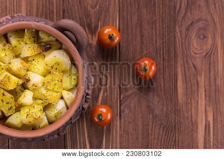 Top View Of Clay Pots With Hot Roast Potatoes And Tomatoes On A Wooden Desk