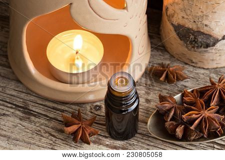 A Dark Bottle Of Star Anise Essential Oil With Star Anise And An Aroma Lamp