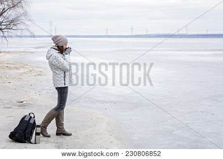 Young Woman Walking On Beach Watching The Frozen Water And Drinks Hot Tea. Walk The River Shore.