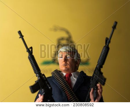 MARCH 11 2018: Caricature of US President Donald Trump brandishing AR 15 semi-automatic assault rifles - Second Amendment concept - NRA - Don't Tread On Me flag
