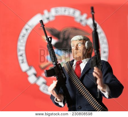 MARCH 11 2018: Caricature of US President Donald Trump brandishing AR 15 semi-automatic assault rifles - Second Amendment concept - National Rifle Association Flag
