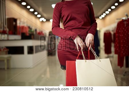 Woman Holding Shopping Bags While Standing On The Mall Background