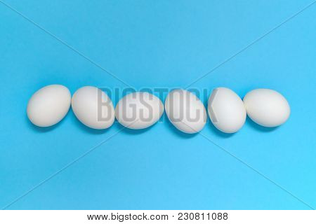 White Eggs On Blue Background, Copy Space. Healthy Food Concept. Top View, Flat Lay. Easter Eggs. Ha